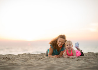 Healthy mother and baby girl laying on beach in the evening