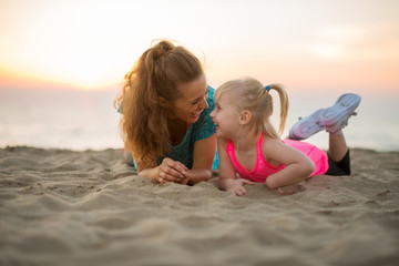 Happy mother and baby girl laying on beach in the evening
