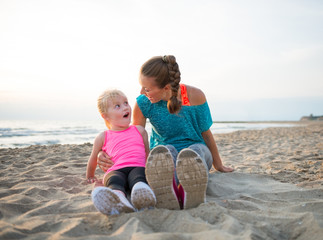 Portrait of fitness mother and surprised baby girl on beach