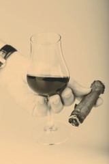 Old brandy in glass and cigar in male hand on white background
