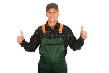 Mature gardener in uniform with thumbs up