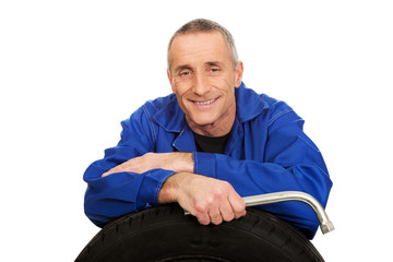 Portrait of happy mechanic with a tire and wrench