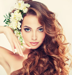 Spring freshness. Girl with delicate pastel flowers in hair