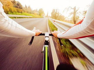 ciclista si allena al tramonto, vista frontale