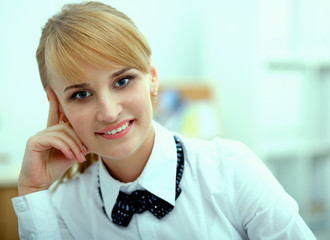 Smiling woman sitting at the desk  in office