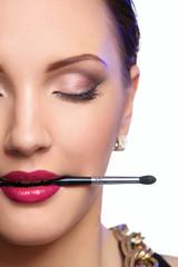Woman's lips holding make up brush