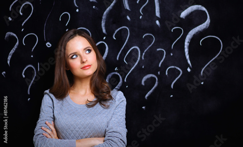 Leinwandbild Motiv Young girl with question mark on a gray background
