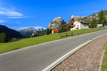 Road along green meadow in Colfosco village, Dolomites Mountains