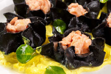 Open black ravioli with salmon