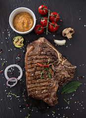 Beef t-bone steak on black stone table