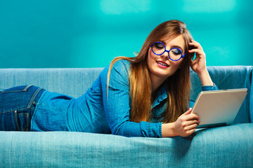 woman with tablet relaxing on couch blue color