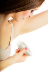 Girl applying stick deodorant in armpit.