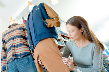 Woman dressing a dummy in a clothes shop