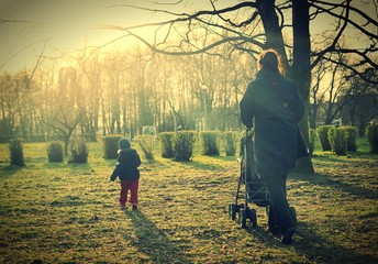Child with mother walking in sunlight. Vintage style.