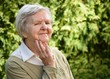 Senior woman smiling and dreaming in garden.