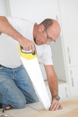 Carpenter using a hand saw