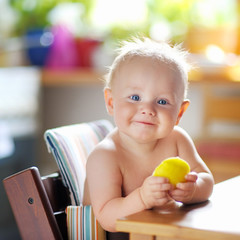 Funny baby boy eating healthy food (apple)