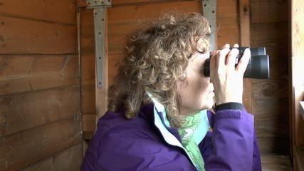 Female bird watcher using a pair of binoculars in a hide