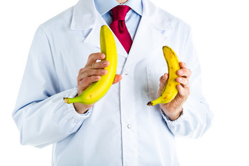 Doctor in white coat showing big and small bananas