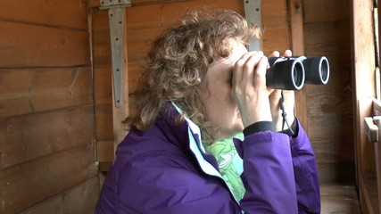 Female bird watcher using a pair of binoculars  looking at birds