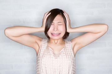 ショック 耳をふさぐ若い女性