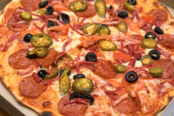 unsliced pepperoni pizza with olives close up view