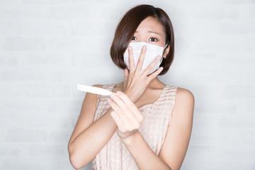 体温計で熱を測る女性
