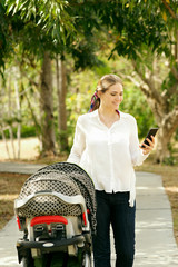 Mother With Baby In Pushchair Sending Message On Phone