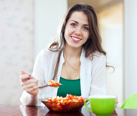 healthy woman eating veggie salad with spoon