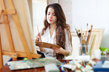 Long-haired female artist paints picture