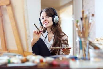 Long-haired girl in headphones  paints  on canvas