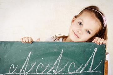 Little child writing on the blackboard