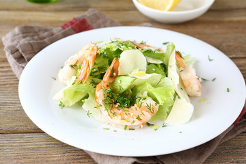 Salad with shrimps, lettuce and cheese on a plate