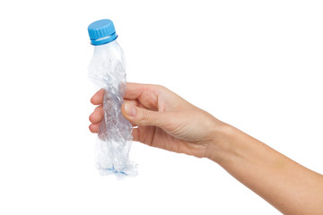 Crushed empty plastic bottle in woman's hand