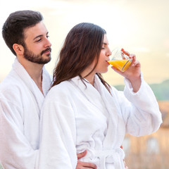 Couple in bathrobe drinking fruit juice.