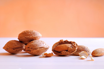 Almonds on a white table and orange background
