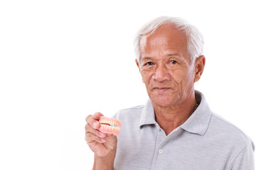 old senior man with hand holding denture