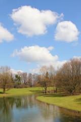 Idyllische Parklandschaft mit Weiher und Schönwetter-Wolken