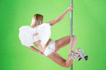 Girl in angelic wings makes  element open knees  at pole dance