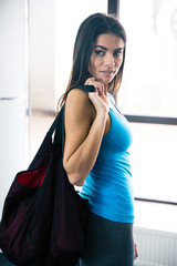 Beautiful fit woman with bag at gym