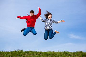 Teenage girl and boy running, jumping outdoor