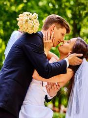 Groom embrace bride .