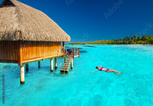 Young woman swimming in tropical lagoon next to overwater villa Poster