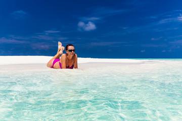 Young woman in purple bikini relaxing on sand on tropical beach