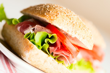 Prosciutto sandwich with tomato and arugula angled view