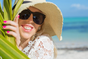Cheerful woman behind palm leaf on the beach