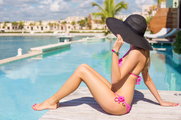 Woman relaxing in luxury resort by the swimming pool