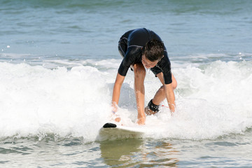 The boy is just beginning to stand up on the surfboard.