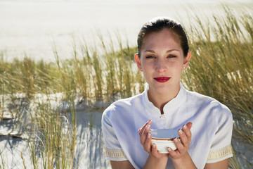 Junge Frau sitzt am Strand, mit einer Teeschale