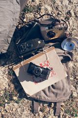 shoulder bag, vintage cameras, and old notebook